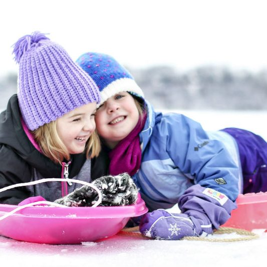 2 little girls on sleds in the snow laughing